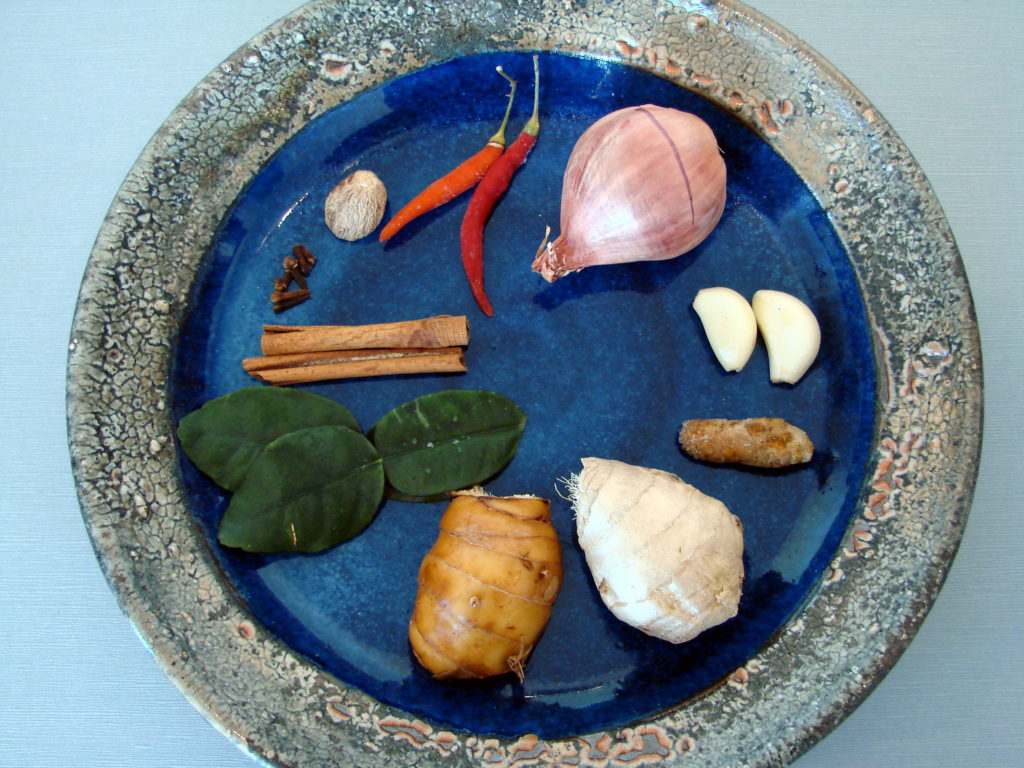 Examples of most of what you'll need for the paste (clockwise from top): Thai chilies, scallion, garlic, fresh turmeric, ginger, galangal, lime leaves, cinnamon sticks, cloves and whole nutmegs.